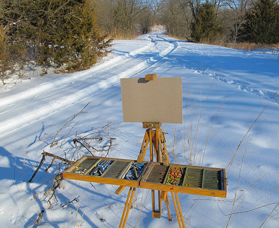 Photo of John Hulsey's plein air pastel set up in the winter snow ready to begin painting